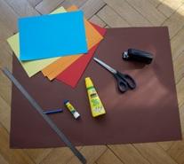 Materialien für den Osterkorb: Bunte Blätter, Flüssigkleber, Tacker, Schere, Lineal und Bleistift