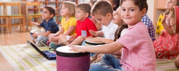 Kinder spielen Musik und malen